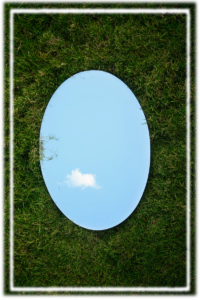 Decorative image of a round mirror on grass, reflecting a blue sky