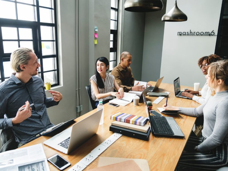Decorative image of diverse group of colleagues in a conference room brainstorming at a table