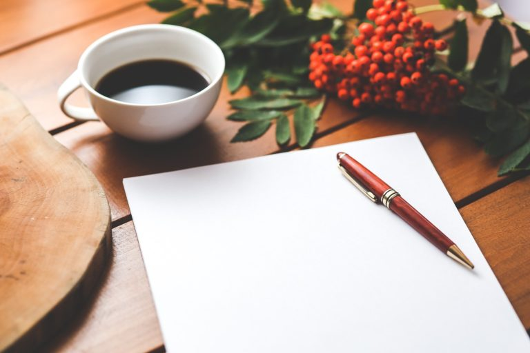 Decorative image including a plant, a cup of coffee, and a pen that is resting on a blank sheet of paper