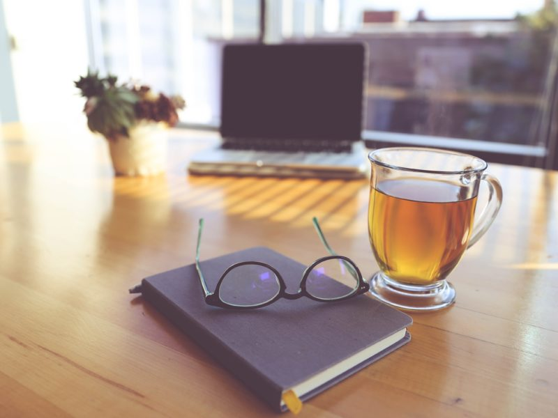 Decorative image of glasses sitting on a notebook next to a cup of tea with a laptop and plant in the background