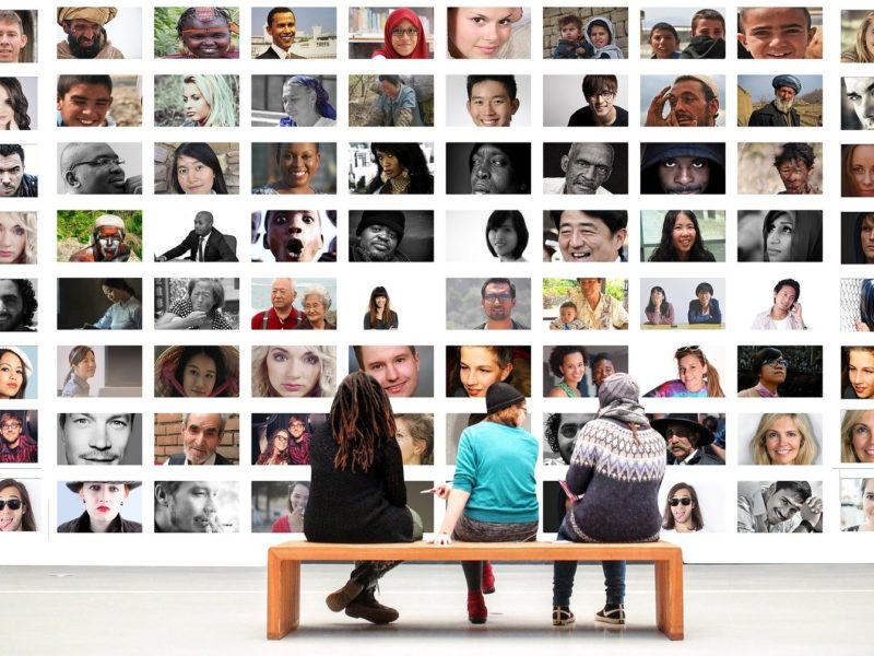 Three people sitting on a bench looking at a large collage of profile pictures of diverse people
